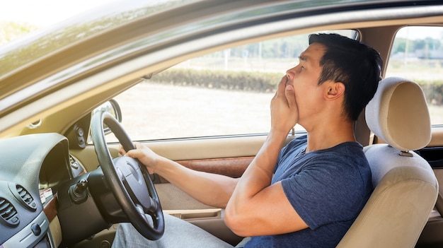 Asian young man driving a car and feel sleepy. Premium Photo