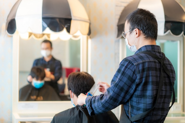 Asian young man and hairdresser man wearing medical mask to protect themselves during novel coronavirus, covid-19 in barbershop hair care service. Premium Photo