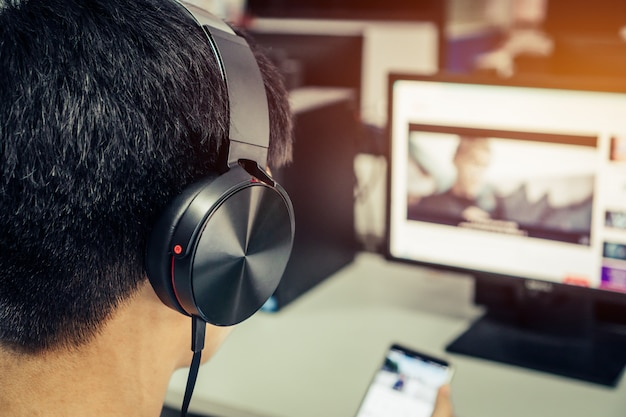 Asian young man listening with headphones and laptop Premium Photo