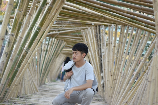 Asian young man sitting in a bamboo arch. Premium Photo