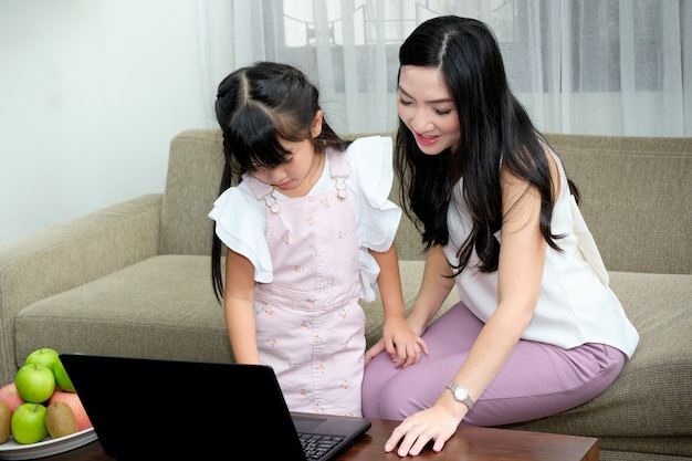 Asian young mother sitting on sofa in the living room with her daughter while is teaching the use of laptop Premium Photo