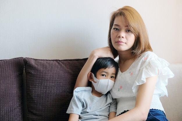 Asian young mother wearing protective  mask for her son at home Premium Photo