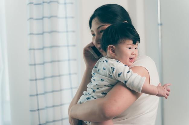 アジアの若い母親の作業とホームオフィスで電話で話しながら赤ちゃんを保持 Premium写真