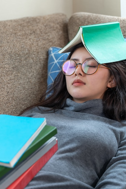 Asian young pretty woman sleeping on couch while stack of books placed on her body Free Photo