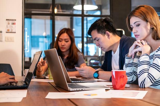 현대 공동 작업 공간 사무실에서 논의하고 협력하는 캐주얼 유니폼을 입은 아시아 젊은 시작 비즈니스 팀. 프리미엄 사진