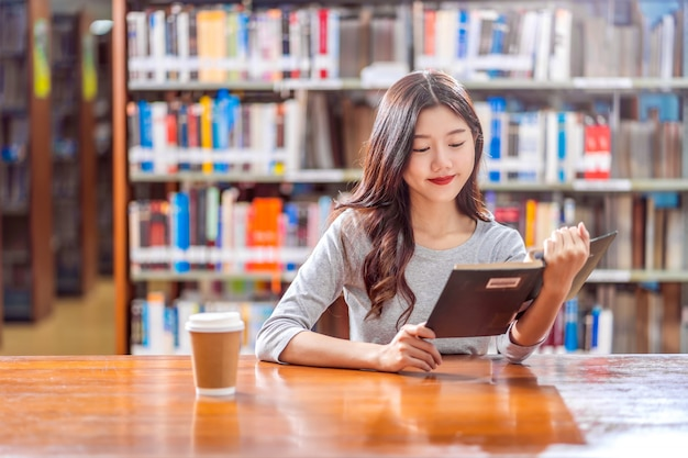 Premium Photo | Asian young student in casual suit reading the book with a  cup of coffee in library of university or colleage on the wooden table over  the book shelf wall,