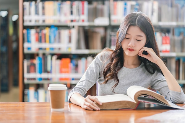 Premium Photo | Asian young student in casual suit reading the book with a  cup of coffee in library of university or colleage