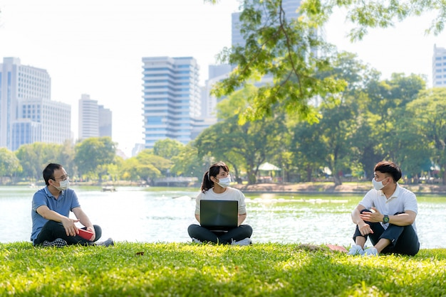 Asian young three man and woman talking and relaxing with they friend and wearing mask sitting distance of 6 feet distance protect from covid-19 viruses for social distancing Premium Photo