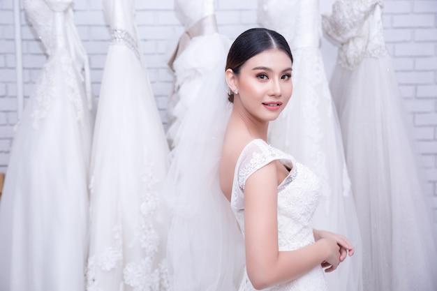 Sposa asiatica della giovane donna che prova sul vestito da sposa alle nozze moderne Foto Gratuite