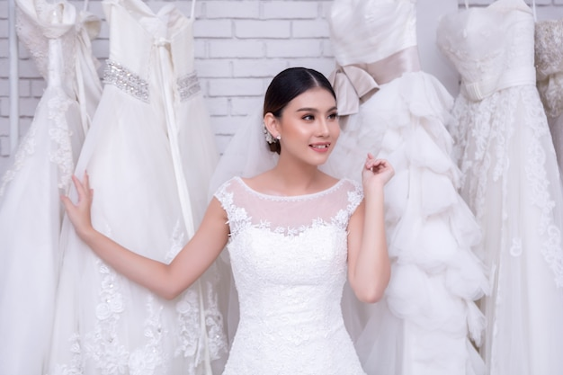 Asian Young Woman Bride Trying On Wedding Dress At Modern