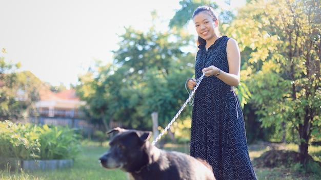 아침에 집에서 뒤뜰 정원에서 산책하는 아시아 젊은 여자 개 프리미엄 사진