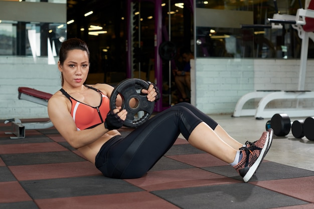 Asian young woman doing exercise with weight plate in a gym Free Photo