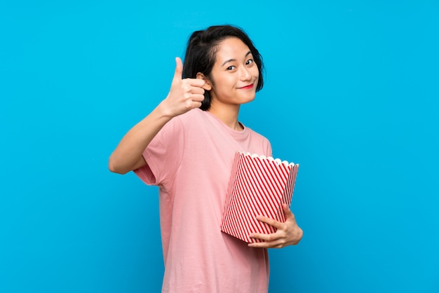 Asian young woman eating popcorns with thumbs up because something good has happened Premium Photo