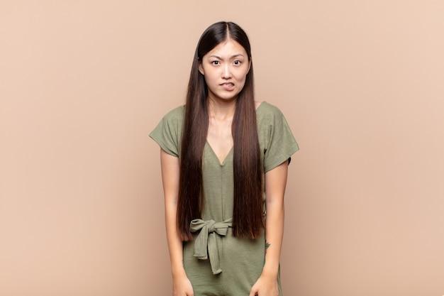 問題を解決しようとして、どのオプションを選ぶべきかについて無知で、混乱し、不確かに感じているアジアの若い女性 Premium写真