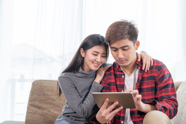 Asian young woman and handsome man sitting on couch using device Free Photo
