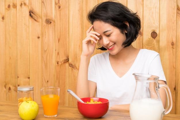 Asian young woman having breakfast milk laughing Premium Photo