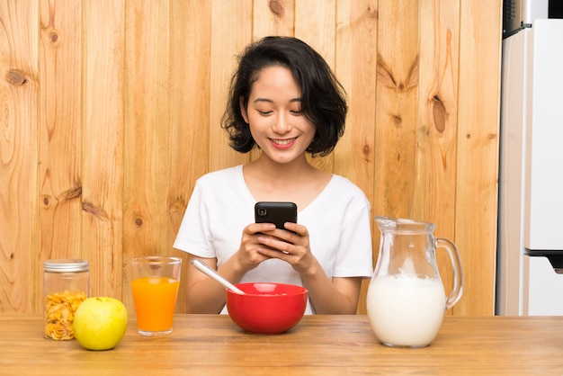 Asian young woman having breakfast sending a message or email with the mobile Premium Photo