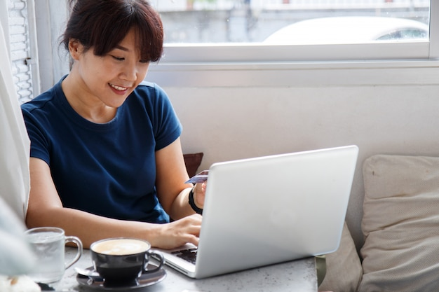 Asian young woman holding credit card mockup and using laptop computer while sitting in cafe. Premium Photo