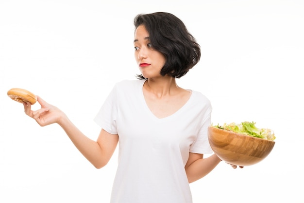 Asian young woman over isolated background with salad and donut Premium Photo