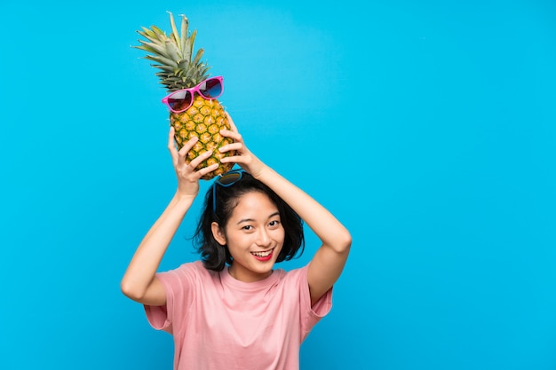 Asian young woman over isolated blue background holding a pineapple with sunglasses Premium Photo