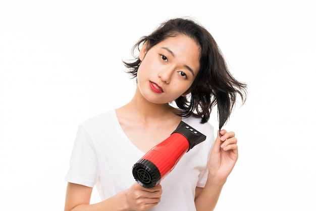 Asian young woman over isolated wall with hairdryer Premium Photo