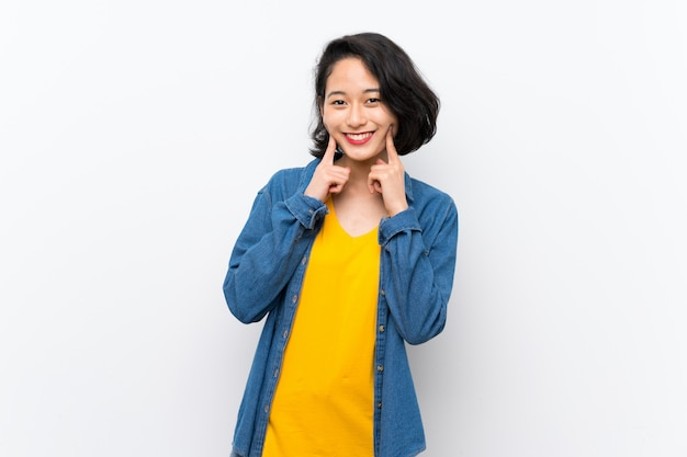 Asian young woman over isolated white smiling with a happy and pleasant expression Premium Photo