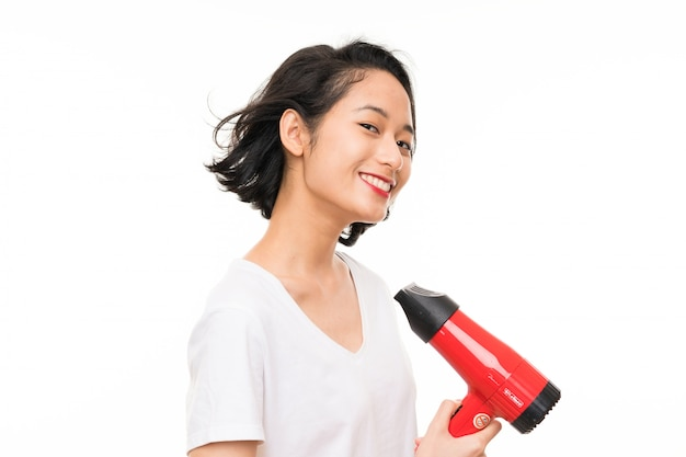 Asian young woman over isolated  with hairdryer Premium Photo