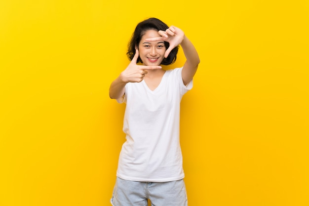 Asian young woman over isolated yellow wall focusing face. framing symbol Premium Photo