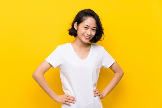 Asian young woman over isolated yellow wall posing with arms at hip and smiling Premium Photo