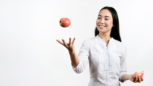 Asian young woman juggling with two red apples 23 2148076218