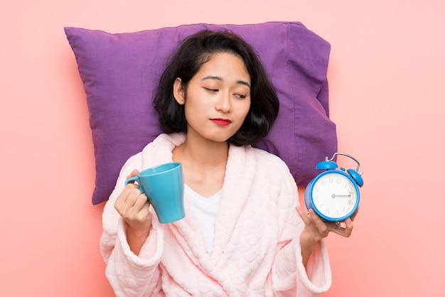 Asian young woman in pajamas holding a cup of coffee and a clock Premium Photo