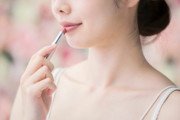 Asian young woman putting red lipstick on her lips | Premium Photo
