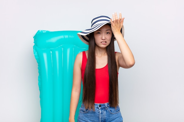 Asian young woman raising palm to forehead thinking oops, after making a stupid mistake or remembering, feeling dumb Premium Photo