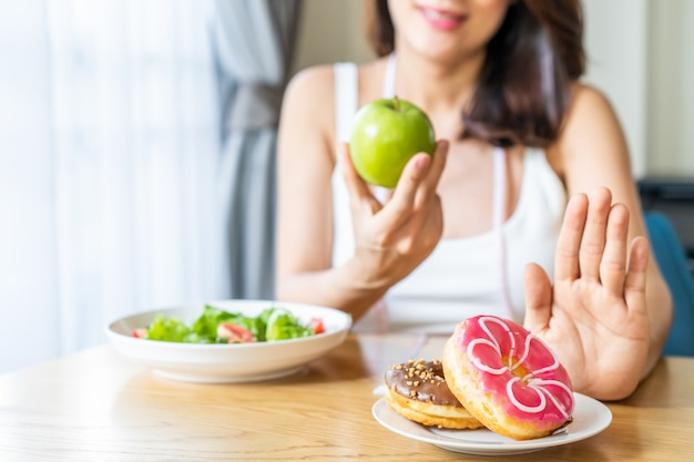 Asian young woman refuse junk food while choose to eat healthy salad and fruit for her healthy. Premium Photo
