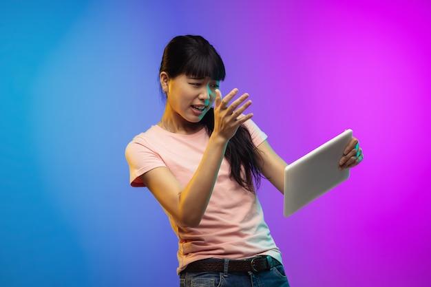 ネオンのグラデーションスタジオの背景にアジアの若い女性の肖像画。カジュアルなスタイルで美しい女性モデル。 無料写真