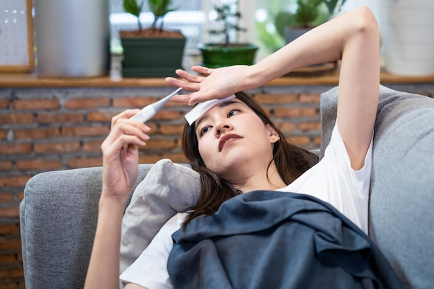 Asian young woman sick with coronavirus or covid-19 having high temperature lying on sofa at home. Premium Photo