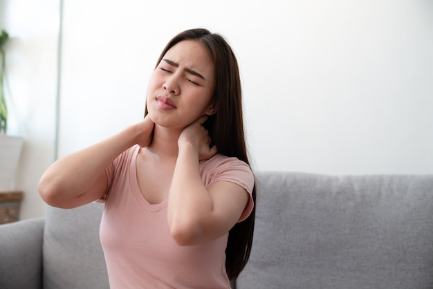 Asian young woman suffering neck pain sitting on sofa couch after finished work at home Premium Photo