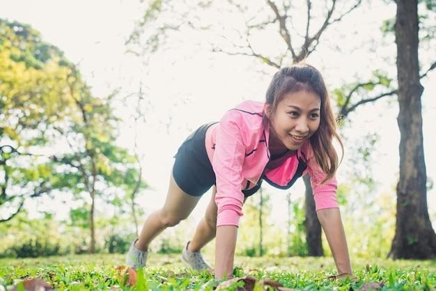아시아 젊은 여성이 그녀의 힘을 키우기 위해 밀어서 몸을 따뜻하게합니다. 프리미엄 사진