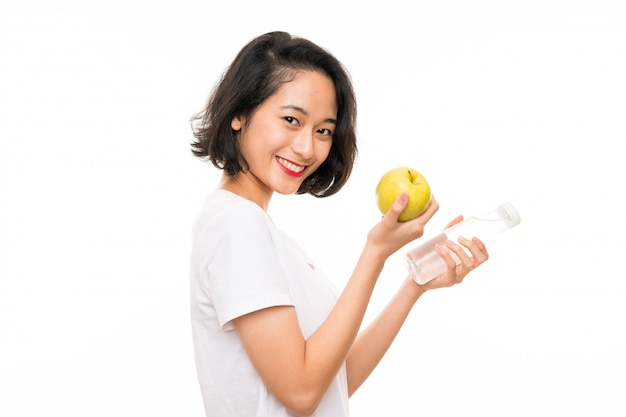 Asian young woman with an apple and bottle of water Premium Photo