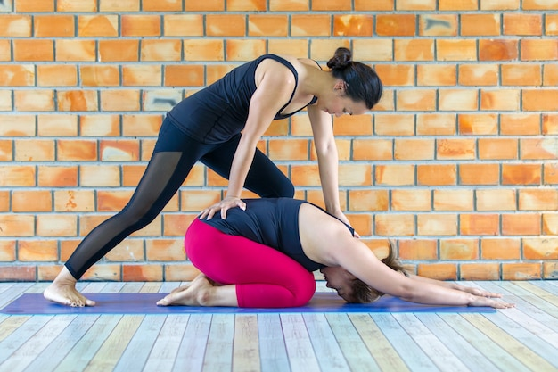 Asians female trainer helping young woman doing yoga. Premium Photo