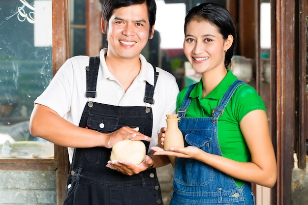 Asians with handmade pottery in clay studio Premium Photo