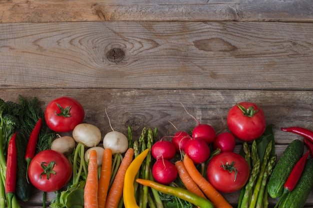 Asparagus, broccoli, chili, tomato, radish, carrots and dill - background of vegetables Premium Photo