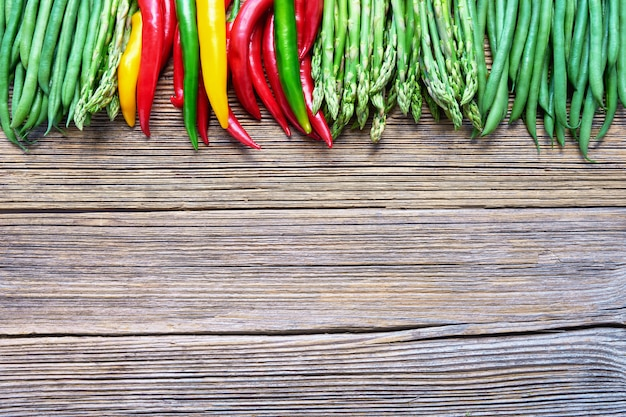 Asparagus, green beans and colorful chilli pepper on rustic wooden background Premium Photo