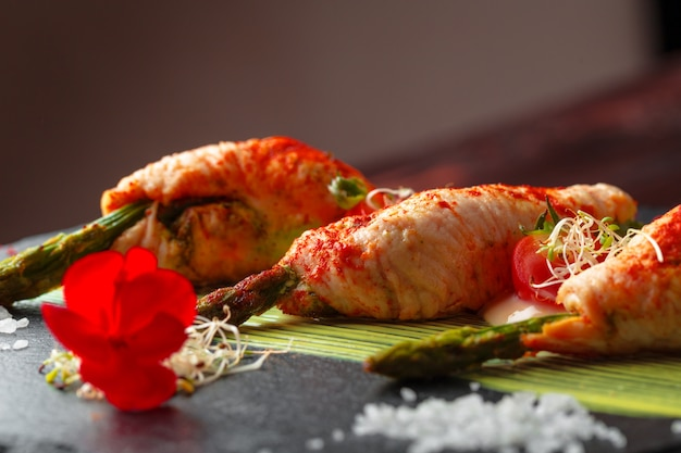 Asparagus rolled with chicken meat slices served on dark plate Premium Photo