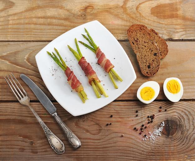 Спаржа в беконе на блюде и яйцо Premium Фотографии