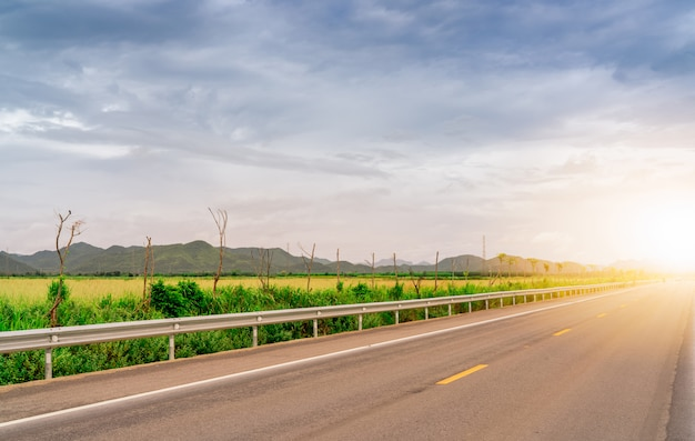 Asphalt road beside green grass field and the mountain with sunlight. long distance journey with blue sky and white cloud. country asphalt road. road trip travel concept. Premium Photo