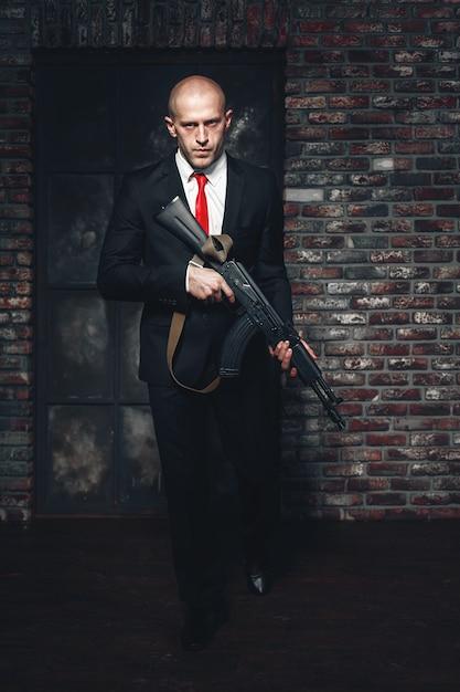 スーツを着た暗殺者と機関銃を手に持った赤いネクタイ。 Premium写真