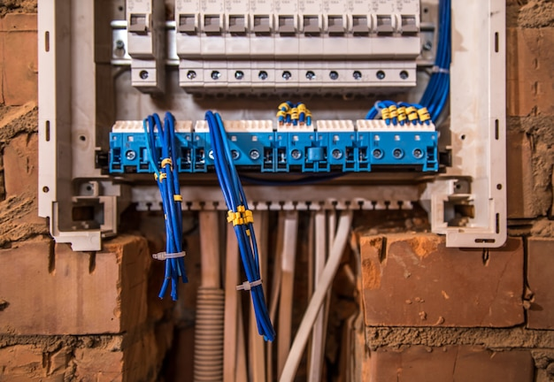 The assembly of the electrical panel, electrician job, a robot with wires and circuit breakers Free Photo