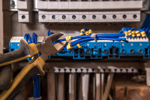 電気パネルの組み立て、電気技師の仕事、ワイヤーと回路ブレーカーを備えたロボット 無料写真