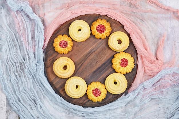 Biscotti assortiti sul piatto di legno con tovaglie rosa e blu. foto di alta qualità Foto Gratuite